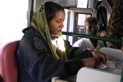 Casher selling tickets in the back of an Asmara public bus
